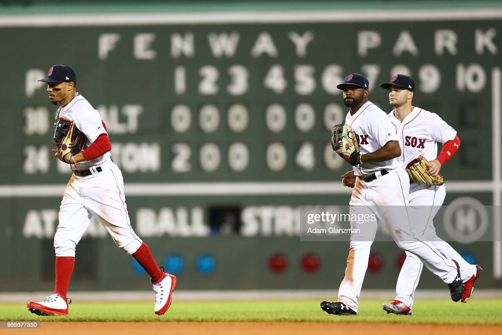 Mookie Betts #50, Jackie Bradley Jr. #19 and Andrew Benintendi #16 of the Boston Red Sox run off the field after a victory over the Baltimore Orioles at Fenway Park on May 17, 2018 in Boston, Massachusetts.