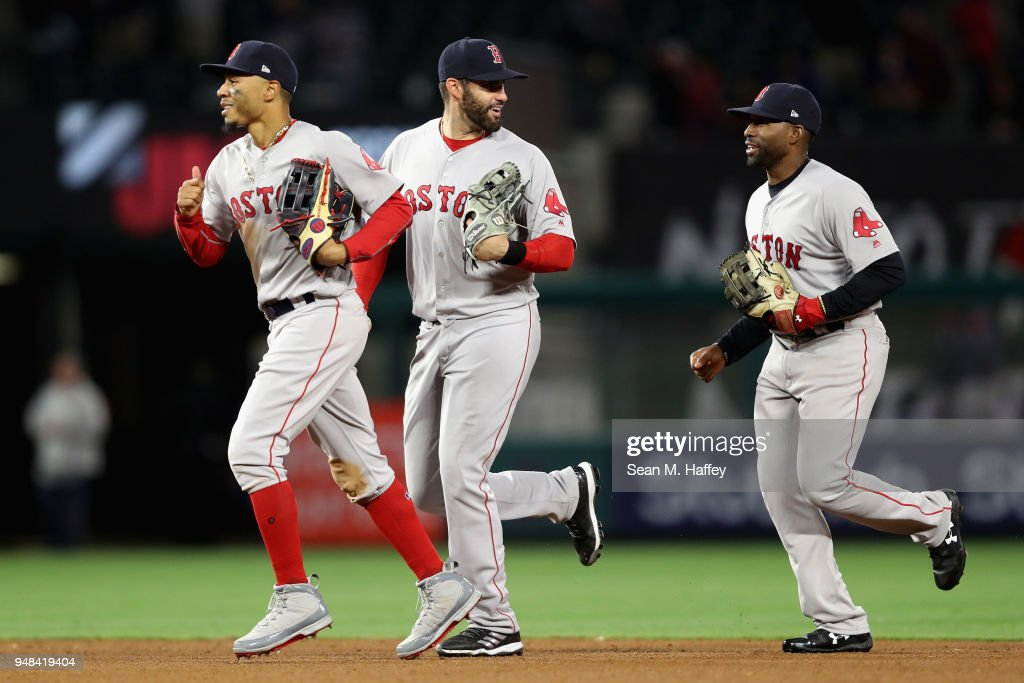 Mookie Betts #50, J.D. Martinez #28 and Jackie Bradley Jr. #19 of the Boston Red Sox celebrate as they run off the field after defeating the Los Angeles Angels of Anaheim 9-0 in a game at Angel Stadium on April 18, 2018 in Anaheim, California.