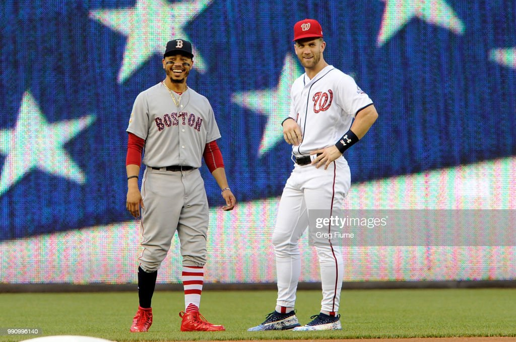 Mookie Betts #50 of the Boston Red Sox and Bryce Harper #34 of the Washington Nationals talk before the game at Nationals Park on July 3, 2018 in Washington, DC.