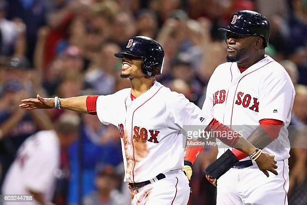 Mookie Betts of the Boston Red Sox and David Ortiz celebrate after scoring runs against the Baltimore Orioles during the first inning at Fenway Park...