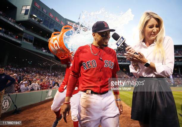 Mookie Betts of the Boston Red Sox and NESN host Guerin Austin are doused in Gatorade after Betts scored the game winning run to defeat Baltimore...
