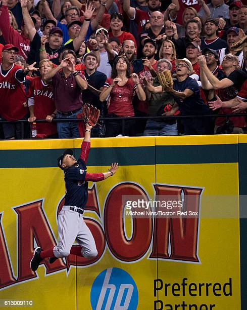 Mookie Betts of the Boston Red Sox attempts to catch a home run hit by Francisco Lindor of the Cleveland Indians in the third inning of game one of...