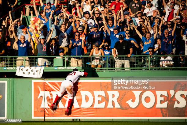 Mookie Betts of the Boston Red Sox attempts to catch a three run home run ball hit by Brandon Nimmo of the New York Mets during the third inning of a...