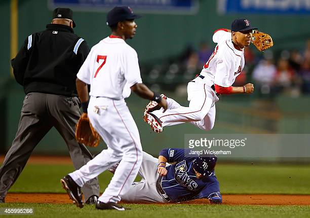 Mookie Betts of the Boston Red Sox attempts to turn the double play over David DeJesus of the Tampa Bay Rays in the first inning during the game at...