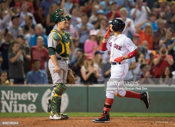 Mookie Betts of the Boston Red Sox blows a kiss towards the stands in front of Dustin Garneau of the Oakland Athletics after hitting a tworun home...