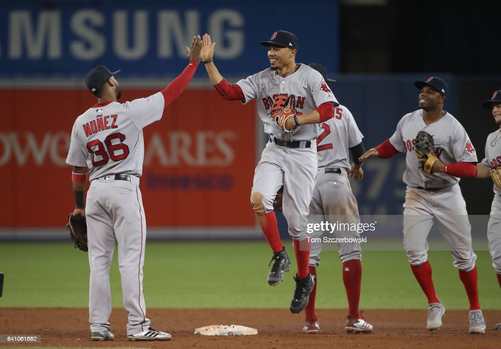 Mookie Betts #50 of the Boston Red Sox celebrates a victory with Eduardo Nunez #36 after MLB game action against the Toronto Blue Jays at Rogers Centre on August 30, 2017 in Toronto, Canada.