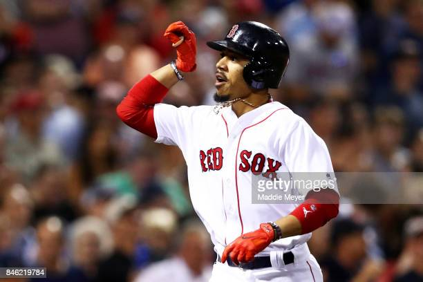 Mookie Betts of the Boston Red Sox celebrates after hitting a two run home run against the Oakland Athletics during the fourth inning at Fenway Park...