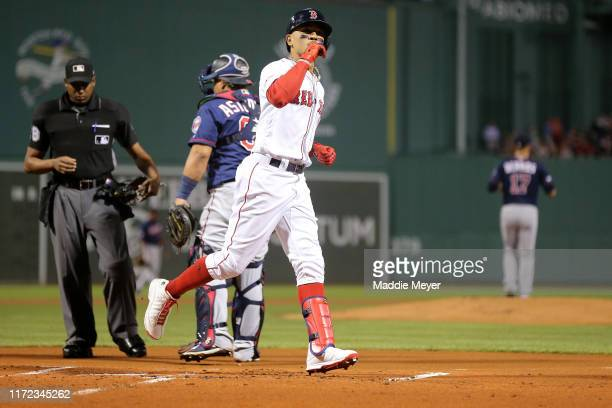 Mookie Betts of the Boston Red Sox celebrates after scoring a home run against the Minnesota Twins during the first inning at Fenway Park on...