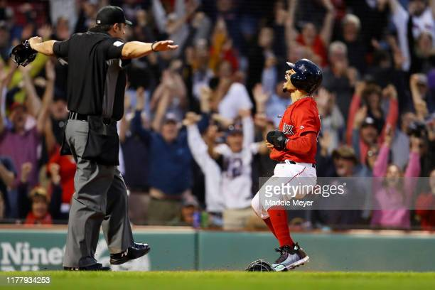 Mookie Betts of the Boston Red Sox celebrates after scoring a run in the ninth inning to defeat the Baltimore Orioles 54 at Fenway Park on September...