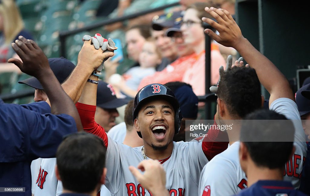 Mookie Betts #50 of the Boston Red Sox celebrates in the dugout after hitting a solo home run against the Baltimore Orioles in the first inning at Oriole Park at Camden Yards on May 31, 2016 in Baltimore, Maryland.