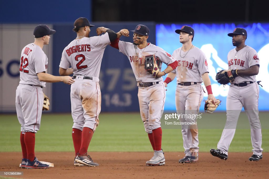 Mookie Betts #50 of the Boston Red Sox celebrates the victory with Xander Bogaerts #2 during MLB game action against the Toronto Blue Jays at Rogers Centre on August 7, 2018 in Toronto, Canada.