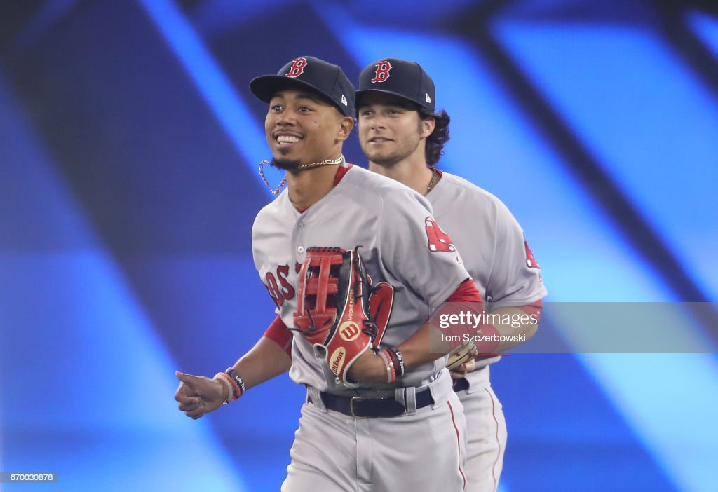 Mookie Betts #50 of the Boston Red Sox celebrates their victory with Andrew Benintendi #16 as they run off the field during MLB game action against the Toronto Blue Jays at Rogers Centre on April 18, 2017 in Toronto, Canada.