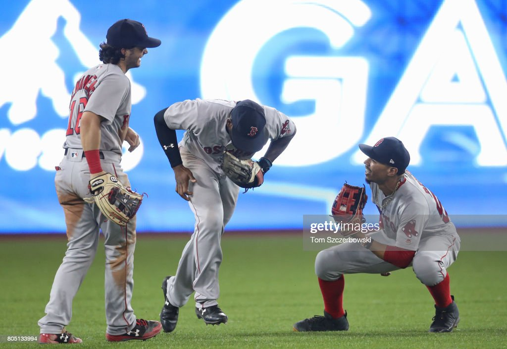 Mookie Betts #50 (R) of the Boston Red Sox celebrates their victory with Jackie Bradley Jr. #19 (C) and Andrew Benintendi #16 during MLB game action against the Toronto Blue Jays at Rogers Centre on June 30, 2017 in Toronto, Canada.