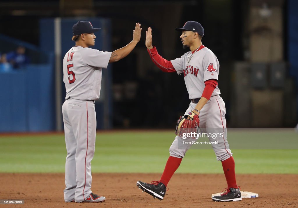 Mookie Betts #50 of the Boston Red Sox celebrates their victory with Tzu-Wei Lin #5 during MLB game action against the Toronto Blue Jays at Rogers Centre on April 26, 2018 in Toronto, Canada.