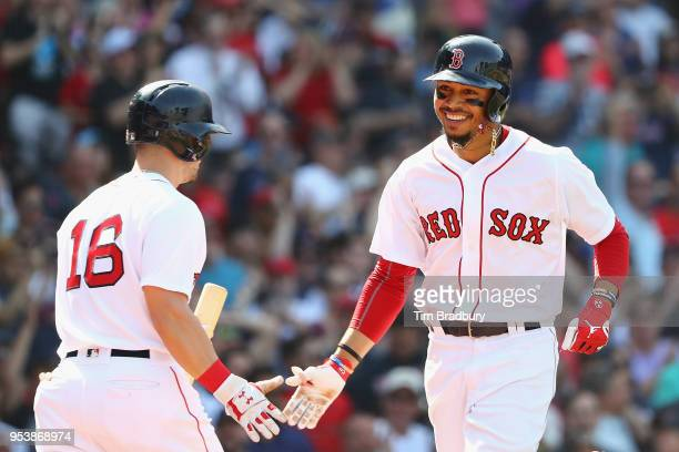 Mookie Betts of the Boston Red Sox celebrates with Andrew Benintendi after hitting a solo home run during the seventh inning against the Kansas City...