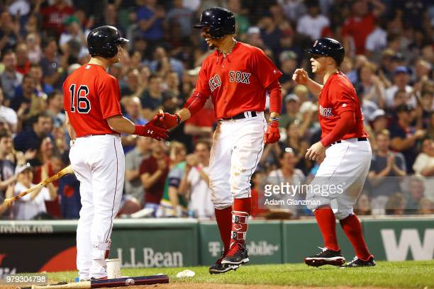 Mookie Betts of the Boston Red Sox celebrates with Andrew Benintendi and Brock Holt after hitting a tworun home run in the seventh inning of a game...