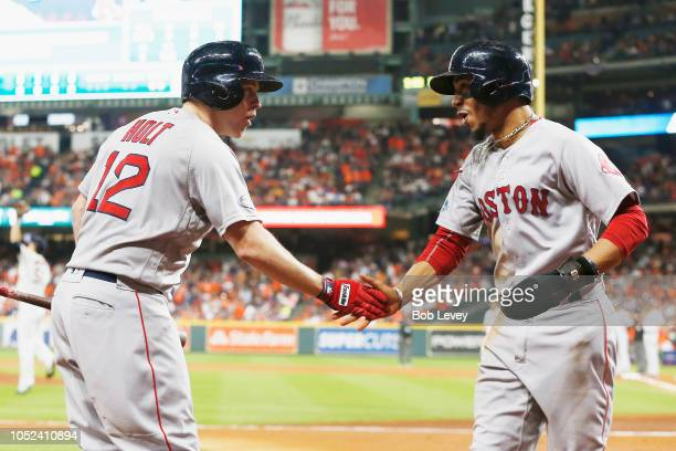 Mookie Betts of the Boston Red Sox celebrates with Brock Holt after scoring a run in the first inning against the Houston Astros during Game Four of...