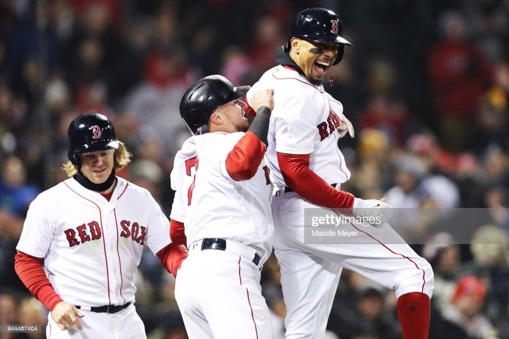 Mookie Betts #50 of the Boston Red Sox celebrates with Brock Holt #12 and Christian Vazquez #7 after hitting a grand slam during the sixth inning against the New York Yankees at Fenway Park on April 10, 2018 in Boston, Massachusetts.