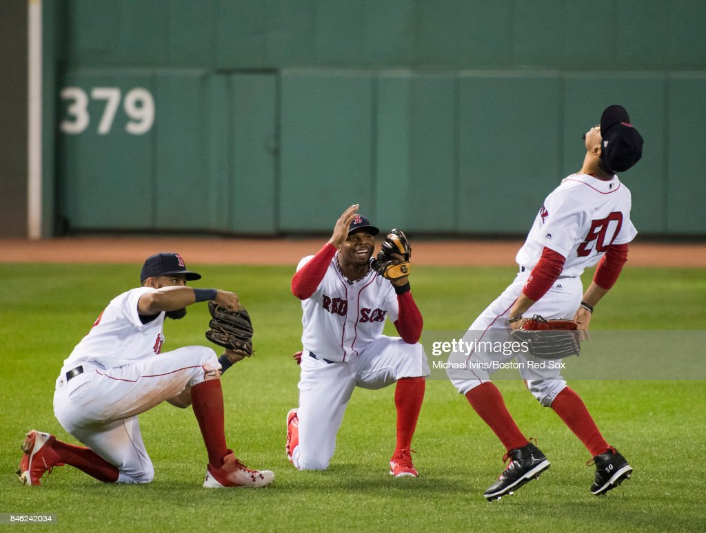 Mookie Betts #50 of the Boston Red Sox celebrates with Chris Young #30 and Rajai Davis #25 after an 11-1 win over the Oakland Athletics at Fenway Park on September 12, 2017 in Boston, Massachusetts. Betts lead the team with two home runs, a triple, six RBI's and three runs scored in the win.