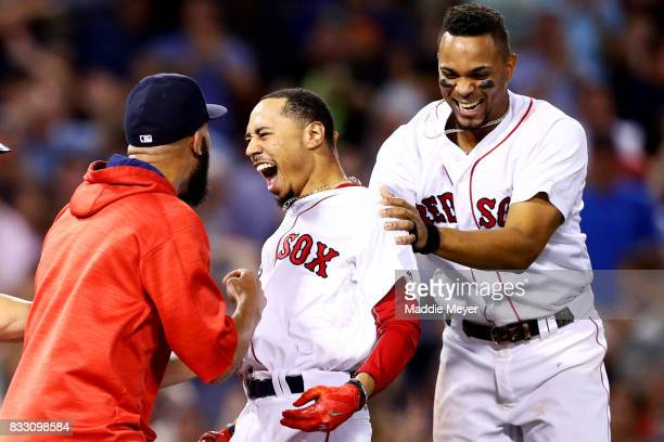 Mookie Betts of the Boston Red Sox celebrates with David Price and Xander Bogaerts after hitting a go ahead two run double to defeat the St Louis...