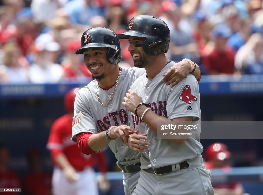 Mookie Betts #50 of the Boston Red Sox celebrates with Deven Marrero #17 after both runners score on a two-run double by Dustin Pedroia #15 in the second inning during MLB game action against the Toronto Blue Jays at Rogers Centre on July 1, 2017 in Toronto, Canada.