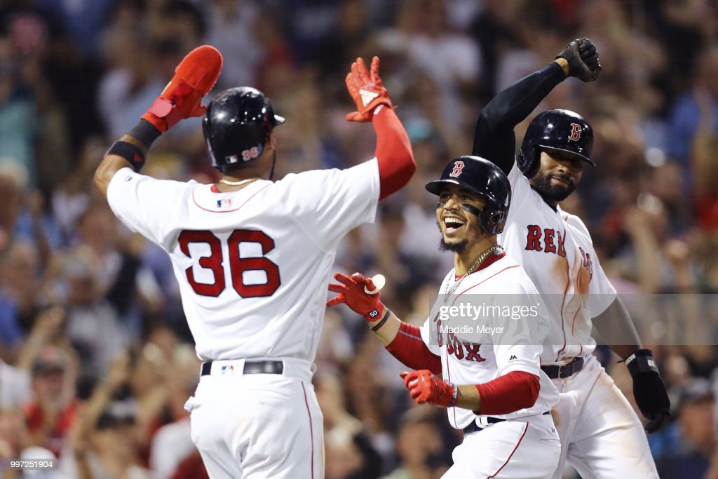 Mookie Betts #50 of the Boston Red Sox celebrates with Eduardo Nunez #36 and Jackie Bradley Jr. #19 after hitting a grand slam against the Toronto Blue Jays during the fourth inning at Fenway Park on July 12, 2018 in Boston, Massachusetts.