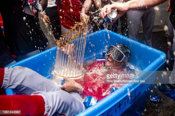 Mookie Betts of the Boston Red Sox celebrates with the World Series trophy as he is dunked in a bucket of beer after winning the 2018 World Series in...