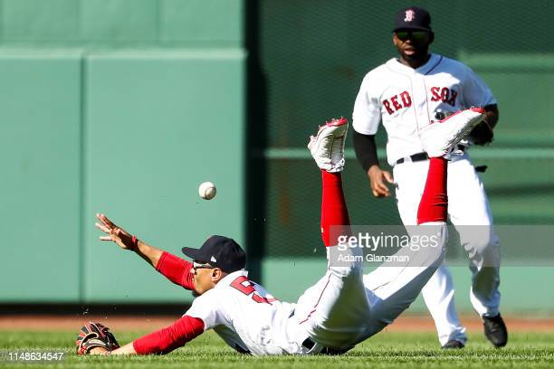 Mookie Betts of the Boston Red Sox dives as he misses a fly ball in the ninth inning during game one of a double header against the Tampa Bay Rays at...