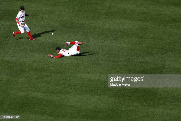 Mookie Betts of the Boston Red Sox dives for a single hit by Logan Morrison of the Tampa Bay Rays which was recovered by Andrew Benintendi during the...