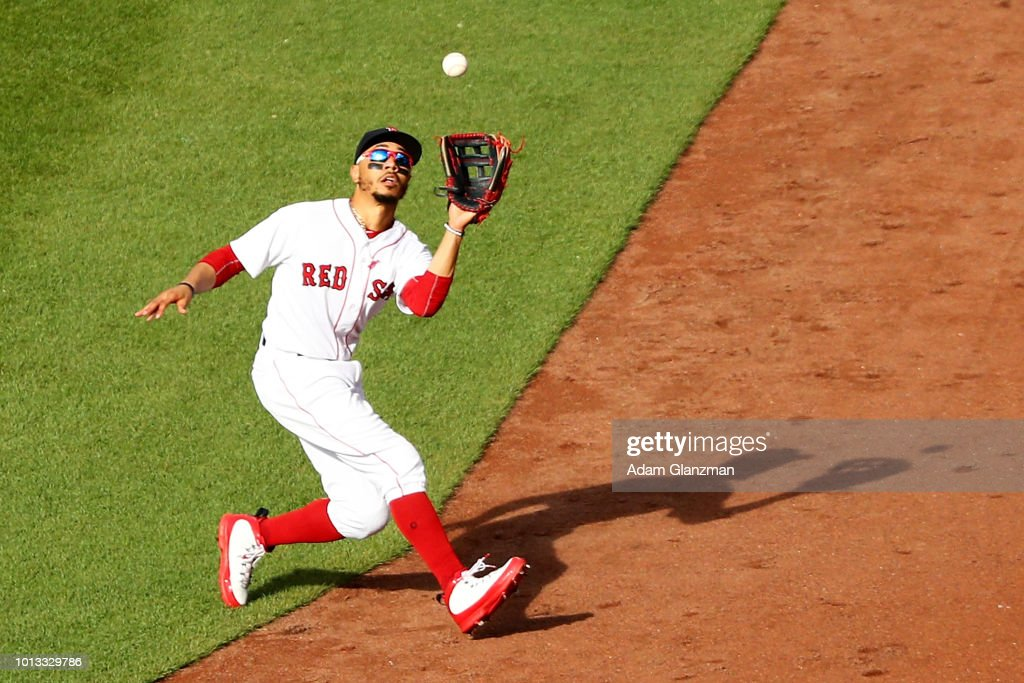 Mookie Betts #50 of the Boston Red Sox fields a fly ball during a game against the New York Yankees at Fenway Park on August 4, 2018 in Boston, Massachusetts.
