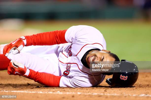 Mookie Betts of the Boston Red Sox grabs for his knee after being hit with the ball at first base during the seventh inning against the Baltimore...