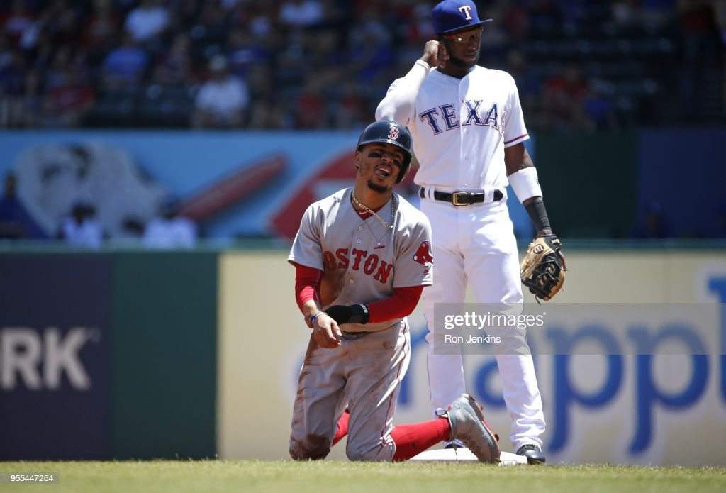 Mookie Betts #50 of the Boston Red Sox grimaces in pain after sliding into second base as Jurickson Profar #19 of the Texas Rangers looks on during the first inning at Globe Life Park in Arlington on May 6, 2018 in Arlington, Texas.
