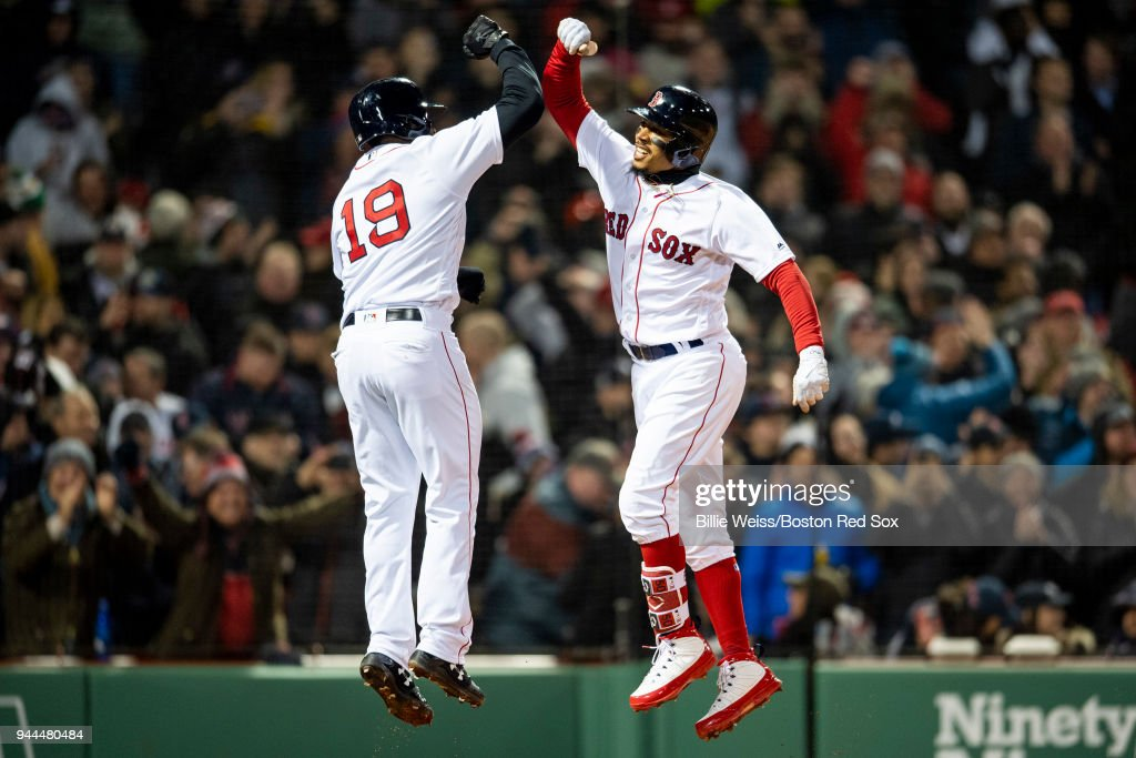 Mookie Betts #50 of the Boston Red Sox high five Jackie Bradley Jr. #19 after hitting a grand slam home run during the sixth inning of a game against the New York Yankees on April 10, 2018 at Fenway Park in Boston, Massachusetts.