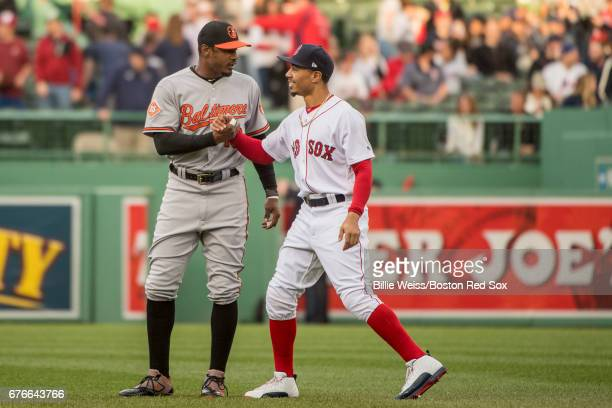 Mookie Betts of the Boston Red Sox high fives Adam Jones of the Baltimore Orioles before a game on May 2, 2017 at Fenway Park in Boston,...