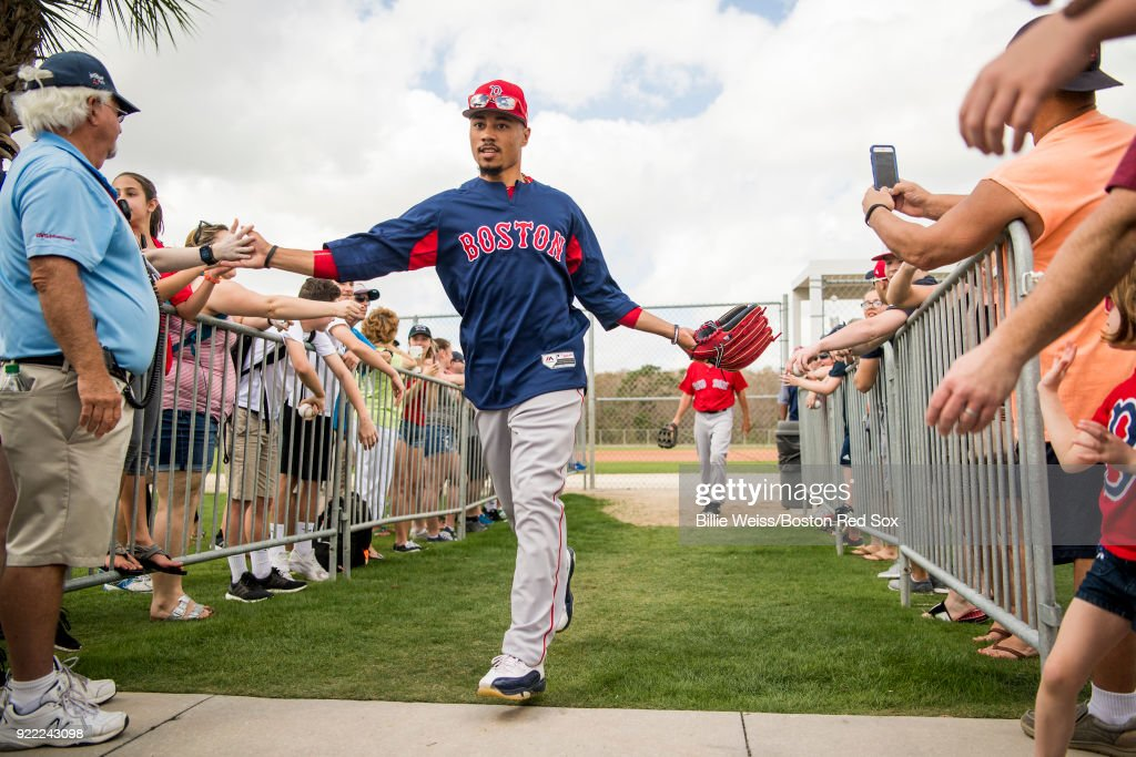 Mookie Betts #50 of the Boston Red Sox high fives fans during a team workout on February 21, 2018 at jetBlue Park at Fenway South in Fort Myers, Florida .