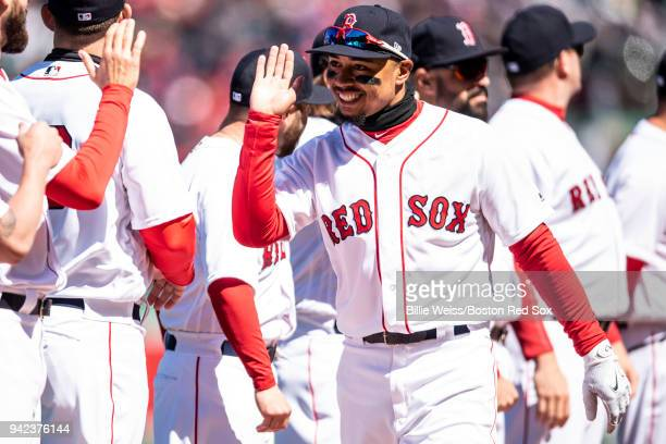 Mookie Betts of the Boston Red Sox high fives teammates as he is introduced before the Opening Day game against the Tampa Bay Rays on April 5 2018 at...