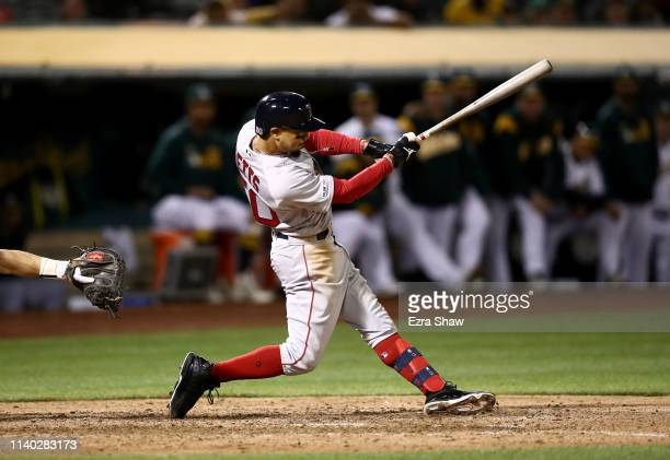 Mookie Betts of the Boston Red Sox hits a double that scored two runs in the ninth inning against the Oakland Athletics at OaklandAlameda County...