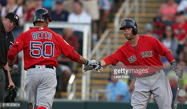 Mookie Betts of the Boston Red Sox hits a first inning home run and is congratulated by teammate Dustin Pedroia during the first inning of the Spring...