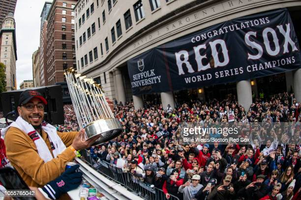 Mookie Betts of the Boston Red Sox holds the World Series trophy as he rides on a duck boat during the 2018 World Series rolling rally parade on...