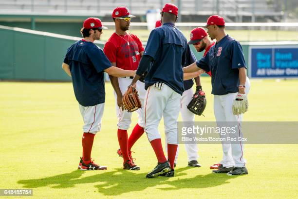Mookie Betts of the Boston Red Sox huddles with Andrew Benintendi Chris Young and other outfielders before a Spring Training game against the Tampa...
