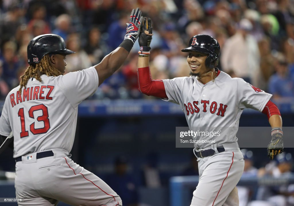 Mookie Betts #50 of the Boston Red Sox is congratulated by Hanley Ramirez #13 after hitting a solo home run in the seventh inning during MLB game action against the Toronto Blue Jays at Rogers Centre on April 18, 2017 in Toronto, Canada.