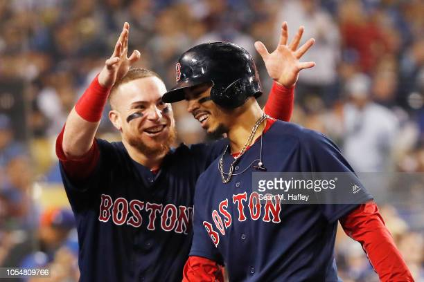 Mookie Betts of the Boston Red Sox is congratulated by his teammate Christian Vazquez after his sixth inning home run against the Los Angeles Dodgers...