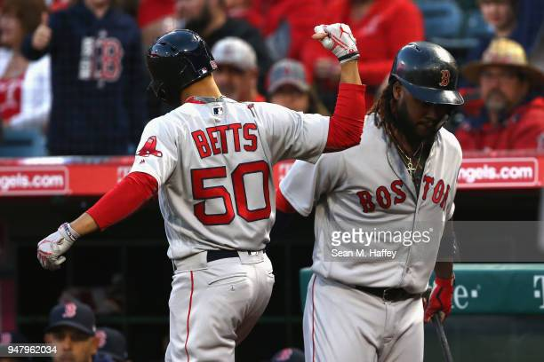 Mookie Betts of the Boston Red Sox is congratulated by JD Martinez of the Boston Red Sox after hitting a solo homerun during the first inning of a...