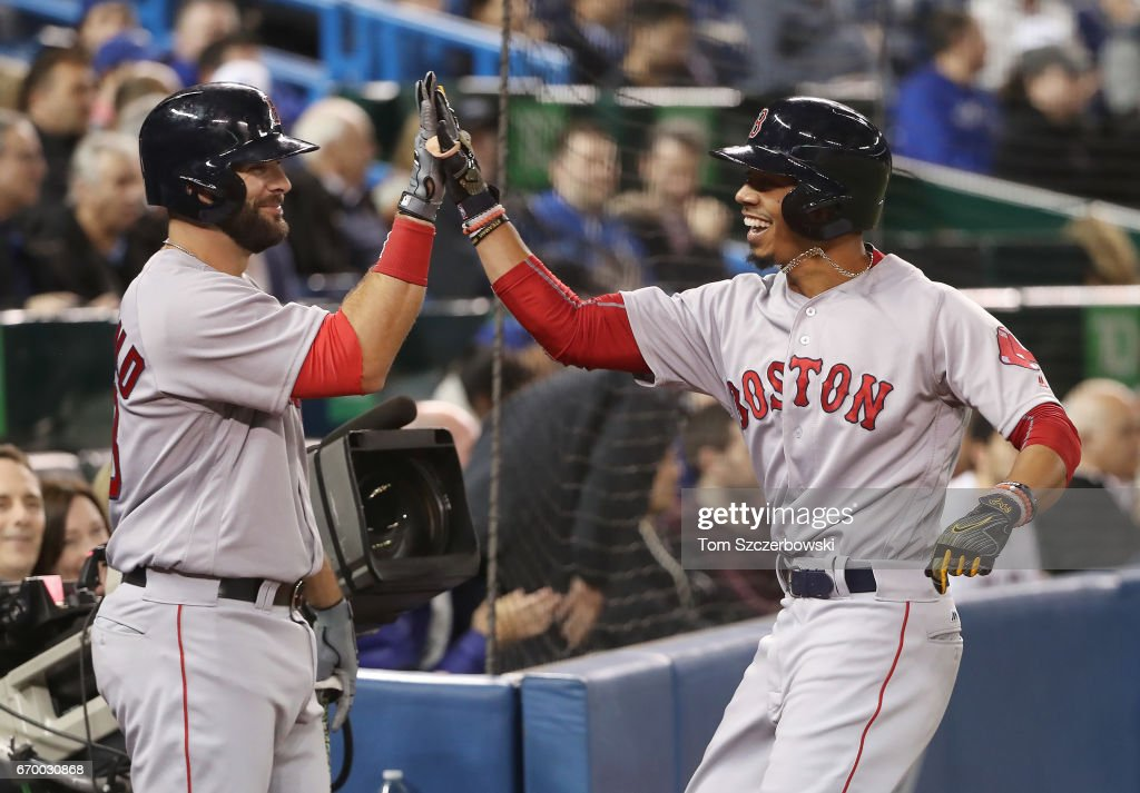 Mookie Betts #50 of the Boston Red Sox is congratulated by Mitch Moreland #18 after hitting a solo home run in the seventh inning during MLB game action against the Toronto Blue Jays at Rogers Centre on April 18, 2017 in Toronto, Canada.