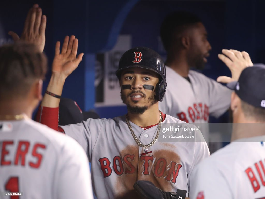 Mookie Betts #50 of the Boston Red Sox is congratulated by teammates in the dugout after scoring a run in the third inning during MLB game action against the Toronto Blue Jays at Rogers Centre on August 8, 2018 in Toronto, Canada.