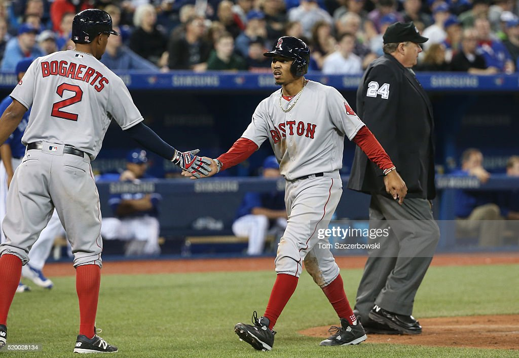 Mookie Betts #50 of the Boston Red Sox is congratulated by Xander Bogaerts #2 after scoring a run in the sixth inning during MLB game action against the Toronto Blue Jays on April 9, 2016 at Rogers Centre in Toronto, Ontario, Canada.