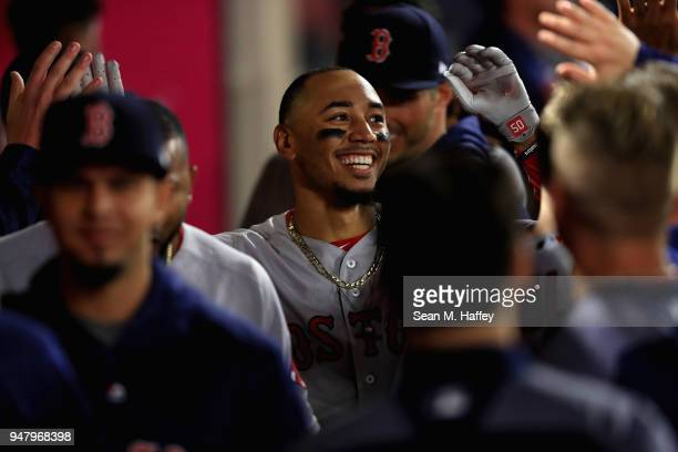 Mookie Betts of the Boston Red Sox is congratulated in the dugout after hitting a solo homerun during the eighth inning his third of a game against...