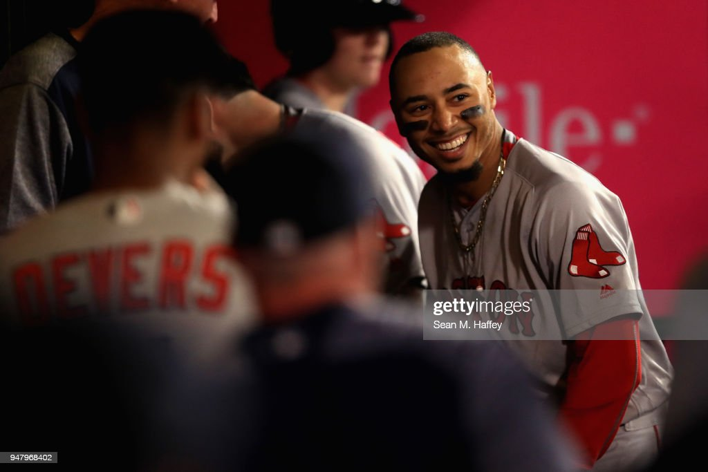 Mookie Betts #50 of the Boston Red Sox is congratulated in the dugout after hitting a solo homerun during the eighth inning, his third of a game against the Los Angeles Angels of Anaheim at Angel Stadium on April 17, 2018 in Anaheim, California.