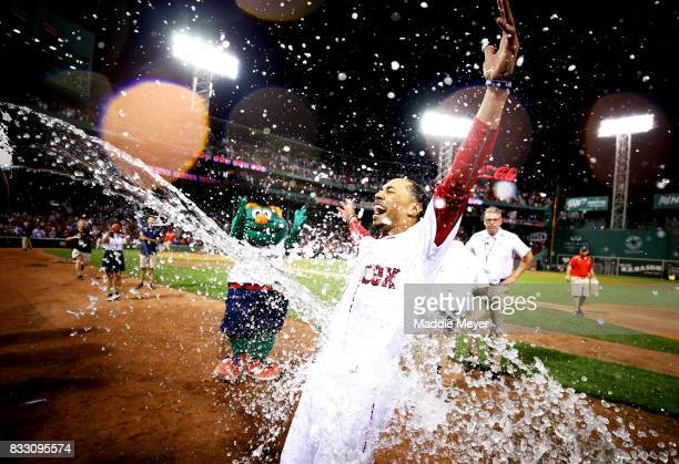Mookie Betts of the Boston Red Sox is doused in water after hitting a walk off two run double to defeat the St Louis Cardinals 54 at Fenway Park on...