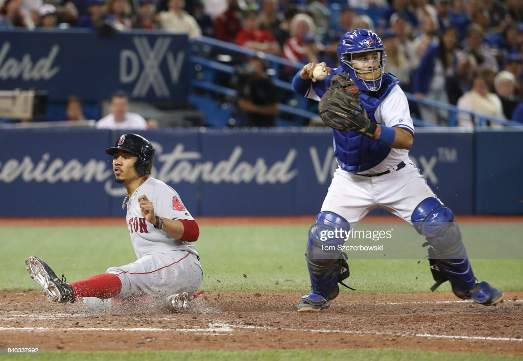 Mookie Betts #50 of the Boston Red Sox is forced out at home plate with the bases loaded in the seventh inning during MLB game action as Raffy Lopez #1 of the Toronto Blue Jays completes the inning-ending double play at Rogers Centre on August 28, 2017 in Toronto, Canada.